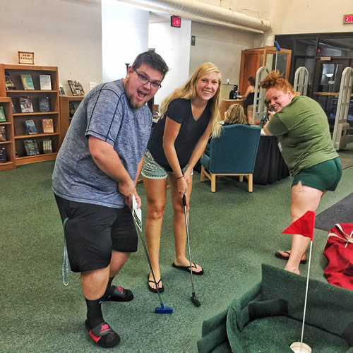 3 students holding golf clubs during Mini Golf event in the Library